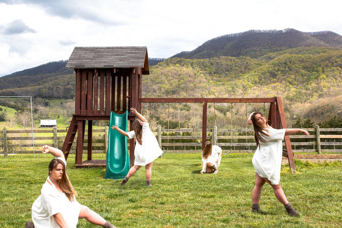 A composite image of four photographs of a woman in white dancing in a yard in front of a playset, with mountains in the background