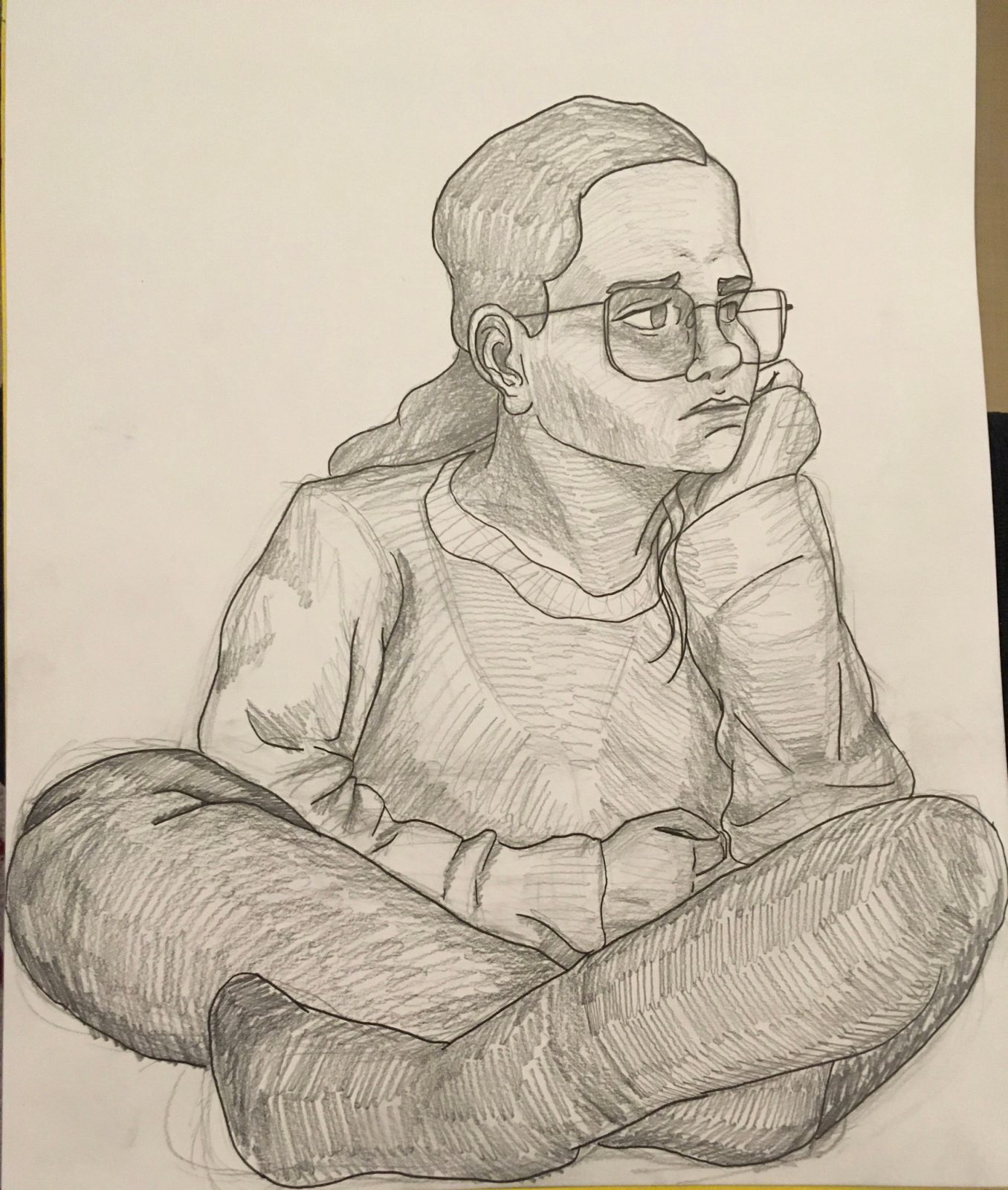 A graphite drawing of a young woman seated on the floor with her legs crossed and her head in her hand