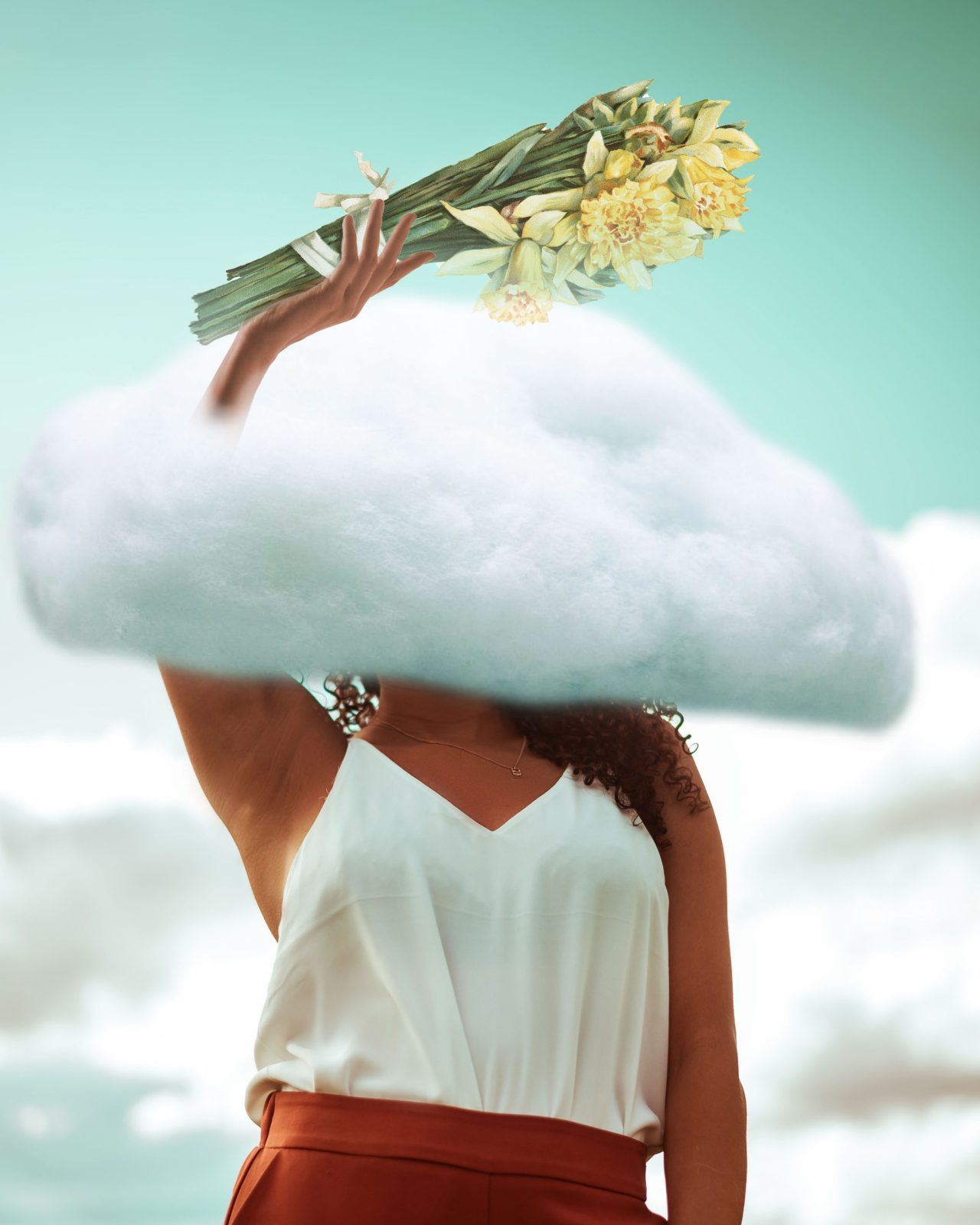A photoshopped image of a brown woman in a white shirt and burnt umber pants against a turquoise background with her head in the clouds and holding a bouquet of daffodils above her head