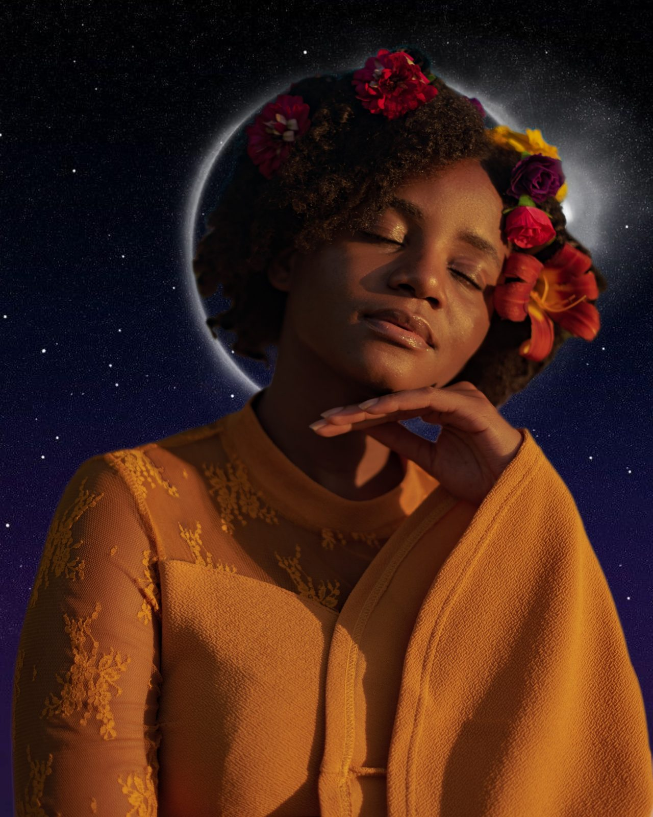 A photograph of a black woman in an orange dress with flowing sleeves wearing a flower crown, her eyes closed peacefully with on hand lightly beneath her chin, and the outline of the moon showing behind her head like an eclipse, against a background of the night sky