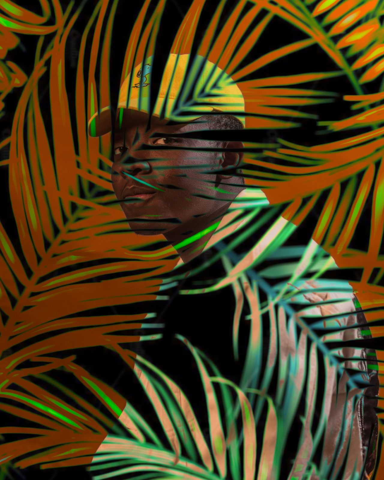 A photograph of a black man in a yellow baseball cap and a peach button down shirt against an orange background making eye contact with the camera and with the figure of a tropical plant with fronds overlaid across the whole image