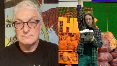 Brian Counihan in black-framed glasses and a black t-shirt, on left, and Olchar Lindsann in a plaid shirt and jeans holding a clipboard with one arm raised above his head in front of lots of art, on the right