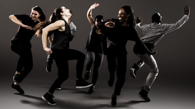A group of six dancers from Ephrat Asherie Dance together on stage in outfits of black and grey