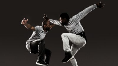 Two Black male dancers from Ephrat Asherie Dance jump into the air while looking towards each other