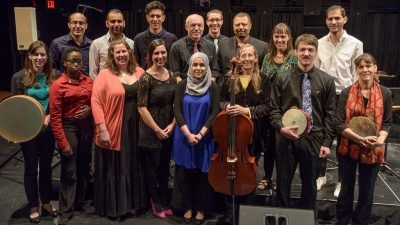 Members of the Itraab Arabic Music Ensemble stand for a group photo backstage at the Moss Arts Center, some holding their instruments