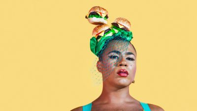 Travis Alabanza wears a turquoise tank top, flawless makeup with a pink lip, and a hat made of three burgers, green ribbon, and teal netting