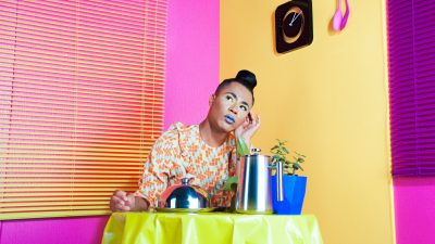 Travis Alabanza sits at a table draped in a yellow cloth with a blue planet with a jade plant inside, a silver teapot, and a plate covered with a silver meal warmer. Alabanza wears a dress with an orange and peach geometric print, a sleep top knot, and flawless makeup, including yellow eyeshadow and an icy blue lip. In the background are a pink and yellow wall, a black clock, two pink serving utentils hung on the yellow wall, and a set of yellow mini blinds hung on the pink wall.
