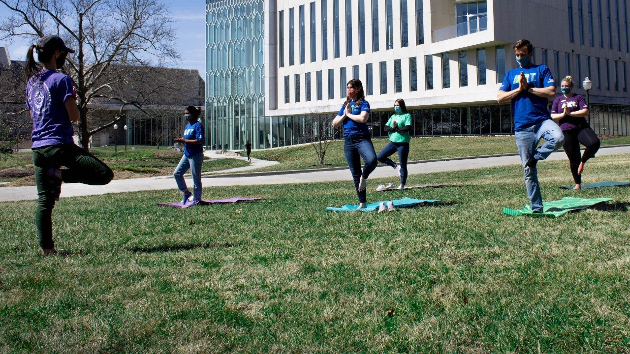 Students practice socially distanced yoga on the lawn outside of the Moss Arts Center