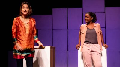 "Two actresses from ""Cartography"" stand on stage. One woman is light brown skinned with shoulder length brown hair and is wearing an orange silk tunic and black pants. The other woman is Black with her braided hair pulled back into a ponytail, and she is wearing a blush colored vest over a dark grey shirt and light pink sweatpants."