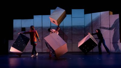 "Some of the cast of ""Cartography"" on stage moving and twirling cardboard boxes against a set backdrop of stacked cardboard boxes with a projection on them"