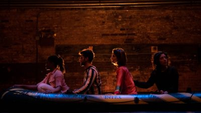 "Four cast members of ""Cartography"" sit in a line inside an inflatable raft on stage"