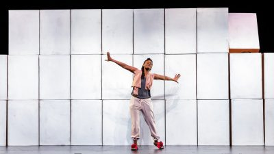 "An actress in ""Cartography"" stands on stage in front of a set background of stacked silver boxes with her arms outstretched. The woman is a black woman with long braids and wearing a pink scarf over a dark grey shirt, light pink sweatpants, and red shoes."