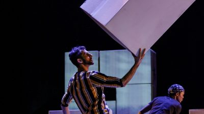 "An actor in ""Cartography"" on stage holding a large silver cardboard box up in one hand. The actor is wearing a multicolor striped shirt and he has dark hair and a short dark beard."