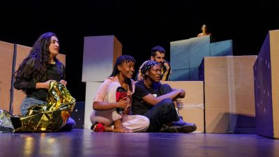 "The cast of ""Cartography"" sits on stage in front of a set background of several cardboard boxes. One woman holds a silver insulated emergency blanket."