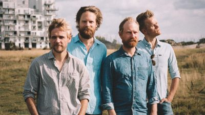 The members of the Danish String Quartet, four white men, stand in a grassy field near a white apartment building on a sunny day. All four are wearing button down shirts in varying shades of blues and light grey, and all four have reddish-blonde hair and beards