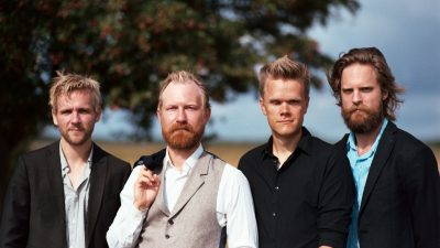 The members of the Danish String Quartet, four white men with reddish-blonde hair, stand in a field with a tree in the background, one in a black blazer with a grey button down shirt, one with a white button down shirt under a grey vest and black blazer slung casually over a shoulder, one in a black button down shirt, and one in a blue button down shirt with a black blazer