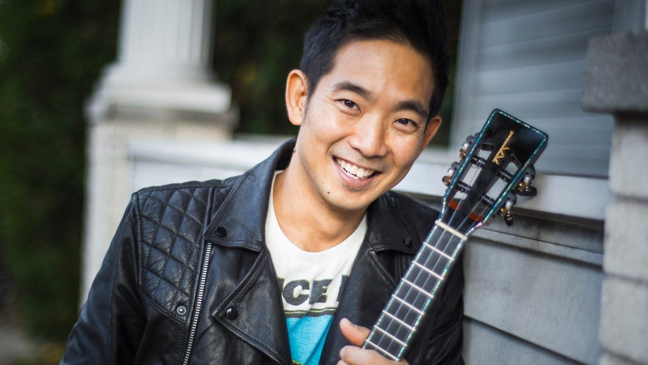 Ukulele master Jake Shimabukuro is a Japanese Hawaiian man wearing a black leather jacket over a concert t-shirt and holding a ukulele outside in front of the side a house