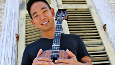 Ukulele master Jake Shimabukuro is a Japanese Hawaiian man wearing a black t-shirt and holding a ukulele outside in front of cream colored wooden shutters