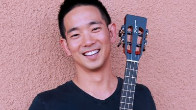 Ukulele master Jake Shimabukuro is a Japanese Hawaiian man wearing a black t-shirt and holding a ukulele in front of a salmon colored stucco wall
