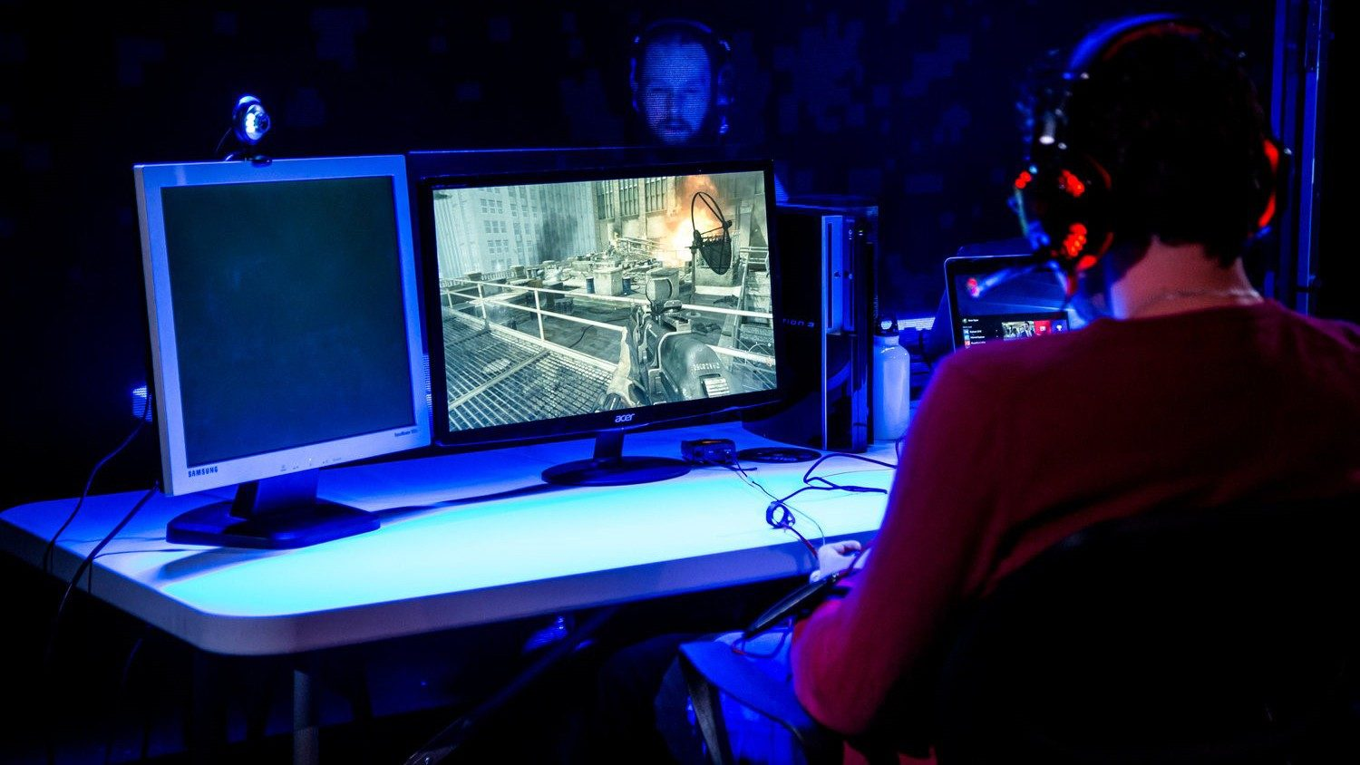 Writer and performer Javaad Alipoor wears red headphones and sits in front of two computer screens on a table, one showing a video game similar to Call of Duty