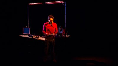 "Writer and performer Javaad Alipoor stands in a dark room in a red shirt as he performs ""The Believers Are But Brothers"""