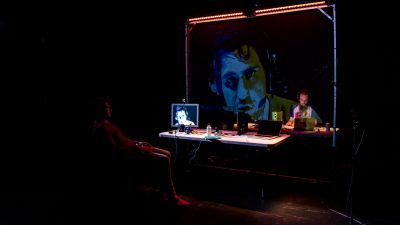 Writer and performer Javaad Alipoor sits at a table with a laptop and two computer screens, one showing his face, which is also projected onto a large semi-transparent screen