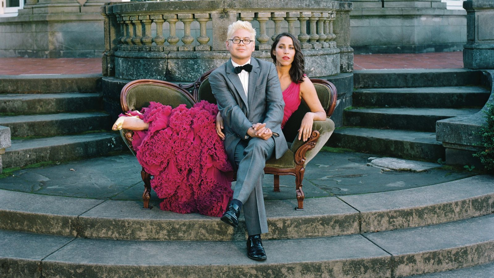 Thomas Lauderdale and China Forbes, who is wearing a pink ball gown, of Pink Martini on an olive green love seat in front of a large house