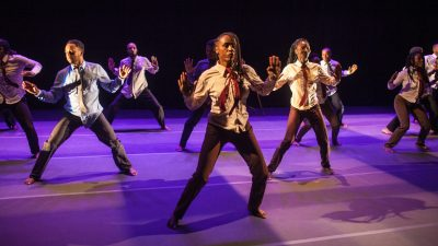 "A group of Colombian dancers in white button down shirts, red ties, and brown pants dance in Sankofa Danzafro's ""The City of Others"""