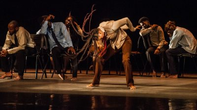 "A group of Colombian dancers in button down shirts, ties, and brown pants dance in Sankofa Danzafro's ""The City of Others"""