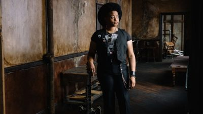 Singer/songwriter Amythyst Kiah, a Black woman with medium length natural hair, stands in an abandoned room. Kiah is wearing a black vest, concert t-shirt, and black pants, and she has a round black hat angled on her head