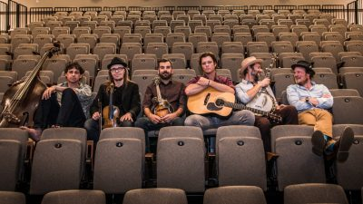 The six members of Steep Canyon Rangers sit with their instruments in their laps or next to them in the seats of a theatre