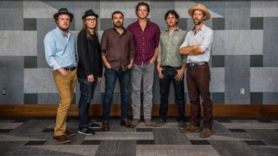The six members of Steep Canyon Rangers stand in a line in front of a grey patterned wall