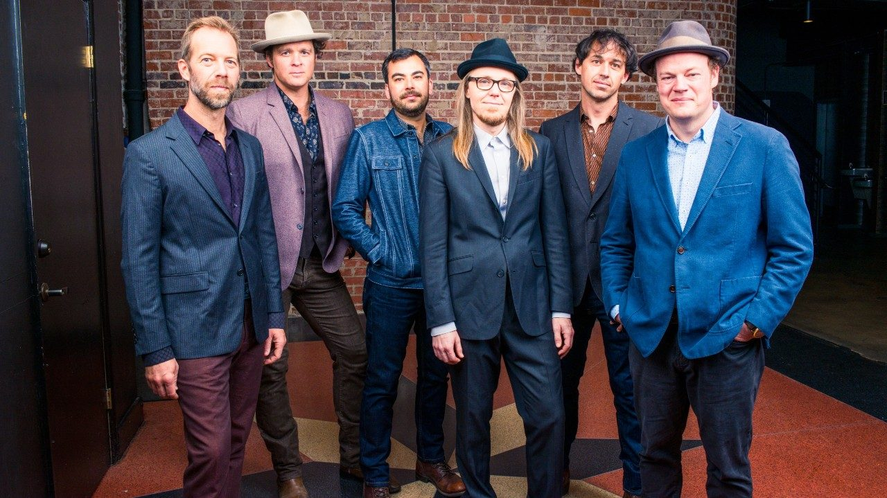 The six members of Steep Canyon Rangers stand in a line in front of a brick interior wall. Five of them are wearing blazers, and three of them are wearing hats.