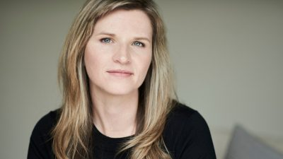 Author Tara Westover, a white woman with long straight blonde hair and hazel eyes, in a black shirt in front of a sage green background